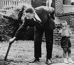 1960, Martin Luther King Jr removing a KKK burned cross from his lawn with his son